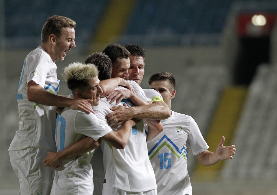 Photo - Slovenia's Josip Ilicic, center, celebrates with his teammates after he scored against Cyprus during their World Cup group E qualifying soccer match at GSP stadium in Nicosia, Cyprus, Tuesday, Sept. 10, 2013.  Slovenia won the match 2-0. (AP Photo/Petros Karadjias)