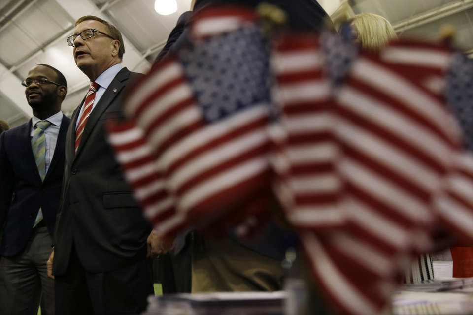 Photo - Republican candidate for Senate Steve Lonegan, second left, walks at a trade show in Flemington, N.J., Tuesday, Oct. 15, 2013, as he campaigns for Senate. Lonegan is running against Democratic Newark Mayor Cory Booker in Wednesday's election. Cory Booker's path to Wednesday's U.S. Senate election has been bumpier than anticipated. Even Republicans had expected Booker, a Democrat in a Democratic-leaning state, to cruise to victory over little-known Steve Lonegan. But the charismatic Newark mayor has faced sustained Republican criticism that has exposed vulnerabilities that could hamper him should he seek higher office someday. (AP Photo/Mel Evans)