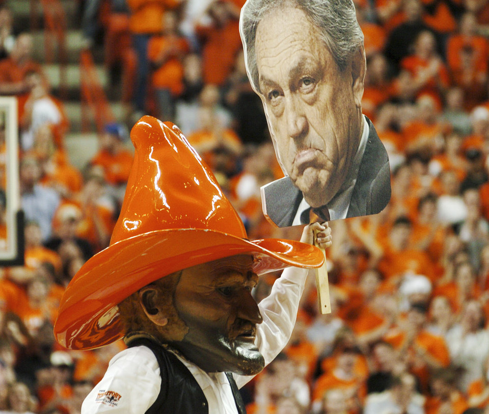 Photo - STILLWATER, OKLA., Feb. 9, 2004: COLLEGE BASKETBALL OKLAHOMA STATE  UNIVERSITY KANSAS UNIVERSITY PLACARD PLACARDS  MASK. Oklahoma State mascot Pistol Pete carries a large face of head coach Eddie Sutton as he gets the OSU fans charged up against KU prior to the first half in Stillwater, Monday, Feb. 9, 2004. Staff Photo by Bill Waugh.