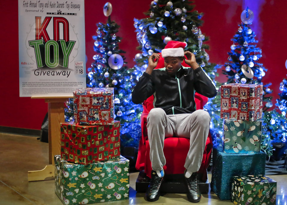 Photo - Kevin Durant adjust his santa hat as he prepares to give out gifts to children during the first annual Tony and Kevin Durant Toy Giveaway at People's Church in Oklahoma City, Okla., Wednesday, Dec. 18, 2013.  .Photo by Chris Landsberger, The Oklahoman