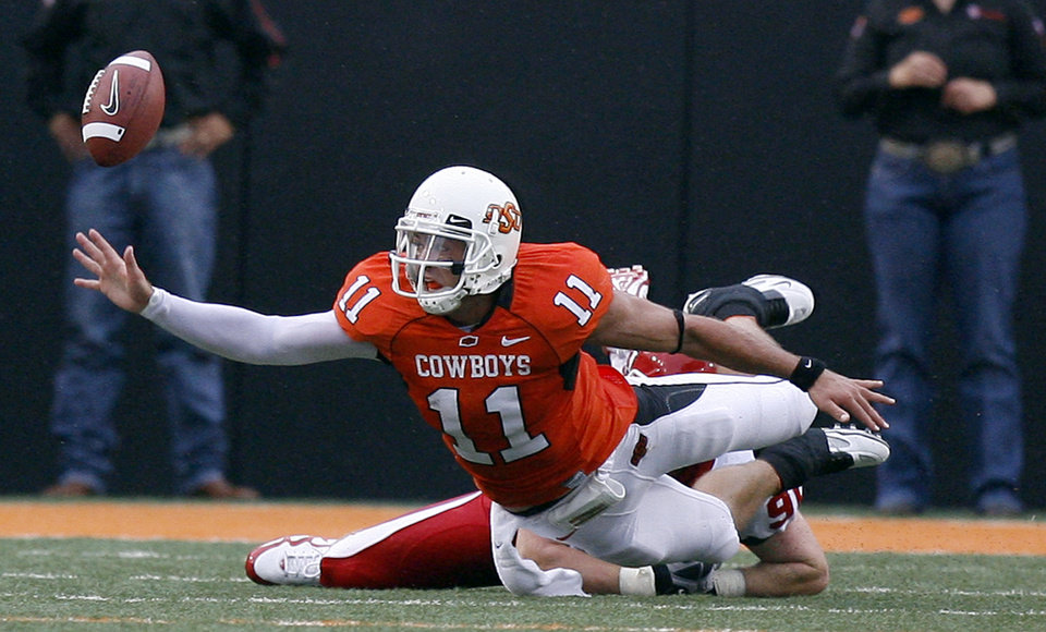Photo - OSU's Zac Robinson (11) fumbles a ball out of bounds as he is tackled by Houston's Zeke Riser (90) during the college football game between the University of Houston (UH) Cougars and the Oklahoma State University (OSU) Cowboys at Boone Pickens Stadium in Stillwater, Okla., Saturday, September 12, 2009. Photo by Sarah Phipps, The Oklahoman ORG XMIT: KOD