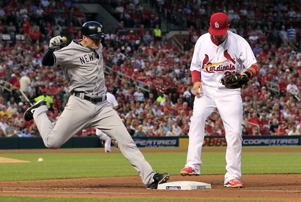 Photo - New York Yankees' Brendan Ryan, left, is out as St. Louis Cardinals first baseman Allen Craig lifts his foot up after tagging the bag during the third inning of a baseball game Wednesday, May 28, 2014, in St. Louis. (AP Photo/Jeff Roberson)