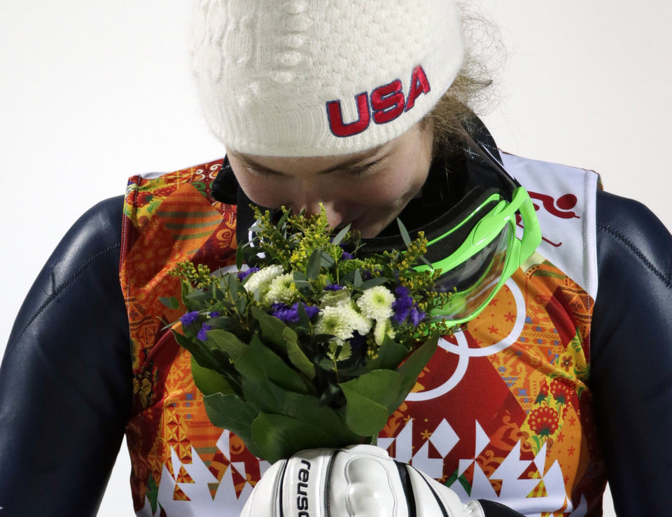 Photo - Women's slalom gold medal winner Mikaela Shiffrin of the United States smells her bouquet during a flower ceremony at the Sochi 2014 Winter Olympics, Friday, Feb. 21, 2014, in Krasnaya Polyana, Russia. (AP Photo/Gero Breloer)