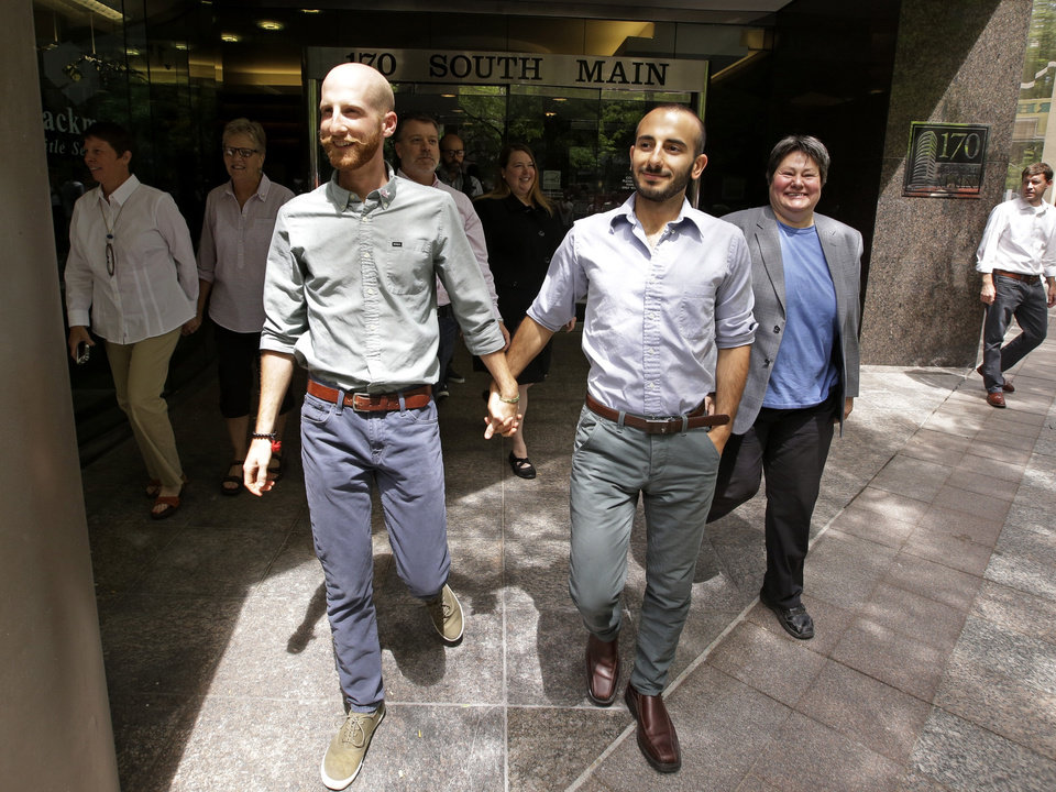 Photo - Plaintiffs Moudi Sbeity, right, and his partner Derek Kitchen, one of three couples who brought the lawsuit against Utah's gay marriage ban, walk with other plaintiffs after arriving for a news conference in Salt Lake City on Wednesday, June 25, 2014. On Wednesday, June 25, 2014, a federal appeals court in Denver ruled that states must allow gay couples to marry, finding the Constitution protects same-sex relationships. The decision from a three-judge panel in Denver upheld a lower court ruling that struck down Utah's gay marriage ban. (AP Photo/Rick Bowmer)
