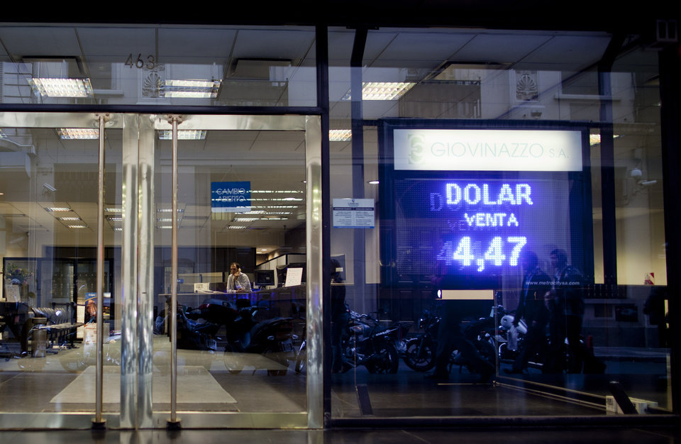 Photo -   A sign shows the official government-set exchange rate of 4.47 Argentine pesos per 1 U.S. dollar at a money exchange house in Buenos Aires, Argentina, Wednesday, May 16, 2012. The AFIP tax collection agency recent measure to control and approve every currency exchange operation in the country has made practically impossible for Argentines to buy dollars, forcing them to get the currency on the black market. (AP Photo/Natacha Pisarenko)