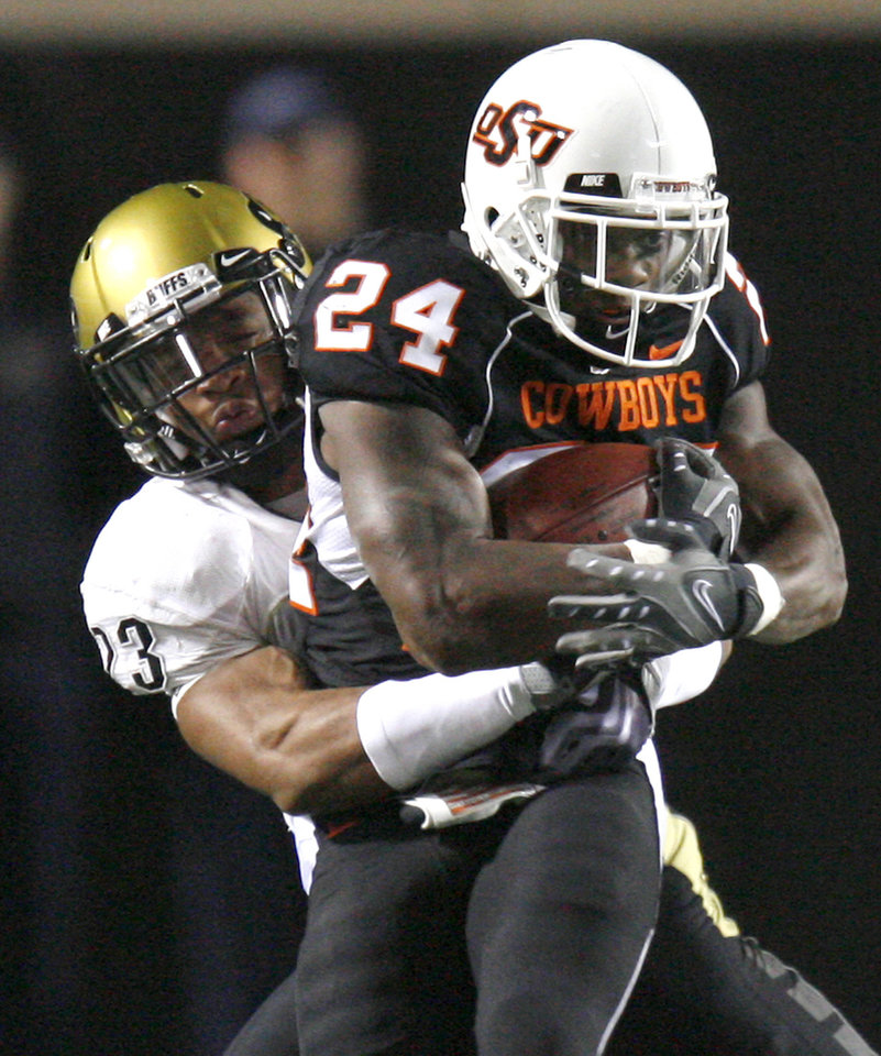 Photo - OSU's Kendall Hunter is brought down by Colorado's Jalil Brown during the college football game between Oklahoma State University (OSU) and the University of Colorado (CU) at Boone Pickens Stadium in Stillwater, Okla., Thursday, Nov. 19, 2009. Photo by Bryan Terry, The Oklahoman