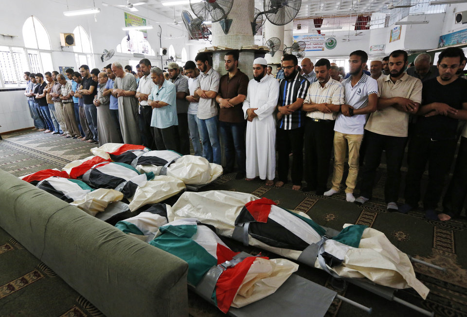 Photo - Palestinians pray at a mosque in front of the national flag-draped bodies of five members of the al-Halaq immediate and extended family, killed Sunday by an Israeli strike at their house in Gaza City, during their funeral at a mosque, Monday, July 21, 2014. On Sunday, the first major ground battle in two weeks of Israel-Hamas fighting exacted a steep price, killing scores of Palestinians and over a dozen Israeli soldiers and forcing thousands of terrified Palestinian civilians to flee their devastated Shijaiyah neighborhood, which Israel says is a major source for rocket fire against its civilians. (AP Photo/Lefteris Pitarakis)