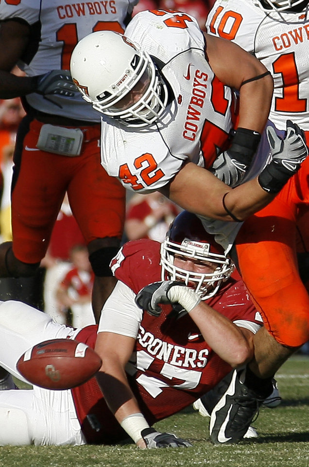 Photo - OSU's Justin Gent fumbles the ball over OU's  Trent  Ratterree during the second half of the Bedlam college football game between the University of Oklahoma Sooners (OU) and the Oklahoma State University Cowboys (OSU) at the Gaylord Family-Oklahoma Memorial Stadium on Saturday, Nov. 28, 2009, in Norman, Okla. Photo by Bryan Terry, The Oklahoman