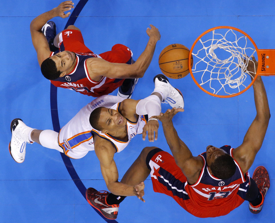 Photo - Oklahoma City's Russell Westbrook (0) goes to the basket between Washington's Garrett Temple, left, and Kevin Seraphin during an NBA basketball game between the Oklahoma City Thunder and the Washington Wizards at Chesapeake Energy Arena in Oklahoma City, Wednesday, March 19, 2013. Oklahoma City won 103-80. Photo by Bryan Terry, The Oklahoman