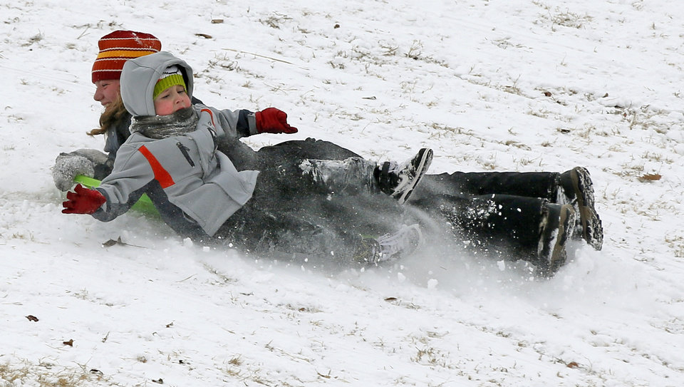 Photo - Alexander Gold, 5, slides off of Jillian Cruise, 13, as they sled down a hill at Douglas Park in Oklahoma City, Friday, Jan. 6, 2017. Photo by Nate Billings, The Oklahoman