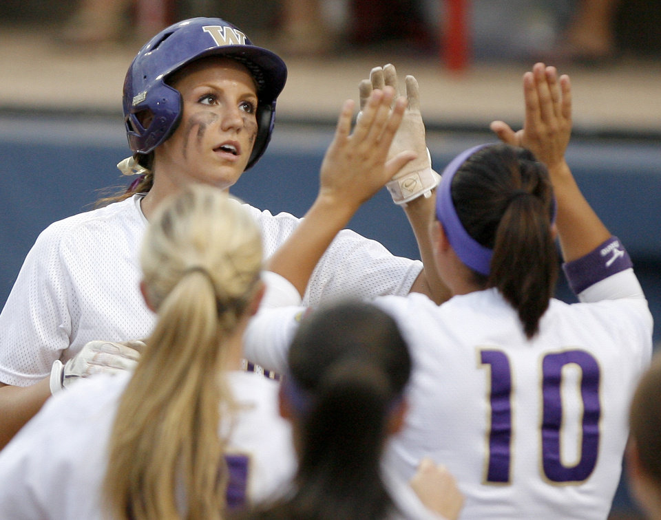 Photo - Washington's Kimi Pohlman celebrates after scoring a the game winning run in the third inning of the second softball game of the championship series between Washington and Florida in Women's College World Series at ASA Hall of Fame Stadium in Oklahoma City, Tuesday, June 2, 2009. Photo by Bryan Terry, The Oklahoman