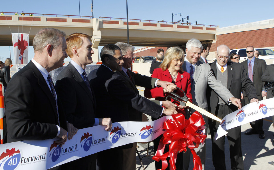 Photo - Gov. Mary Fallin, center, with a pair of large scissors cutting the ribbon during grand opening ceremonies for the east bound lanes of the I-40 Crosstown in Oklahoma City Thursday, Jan. 5, 2012. Photo by Paul B. Southerland, The Oklahoman ORG XMIT: KOD