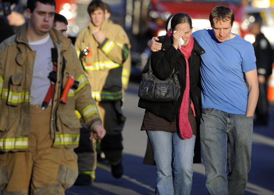 Robert and Alissa Parker, at right, leave a firehouse staging area following a shooting at the Sandy Hook Elementary School in Newtown, Conn., where authorities say a gunman opened fire, killing 26 children and adults at the school, including the Parkers\' daughter Emilie Parker, 6, Friday, Dec. 14, 2012. (AP Photo/Jessica Hill)