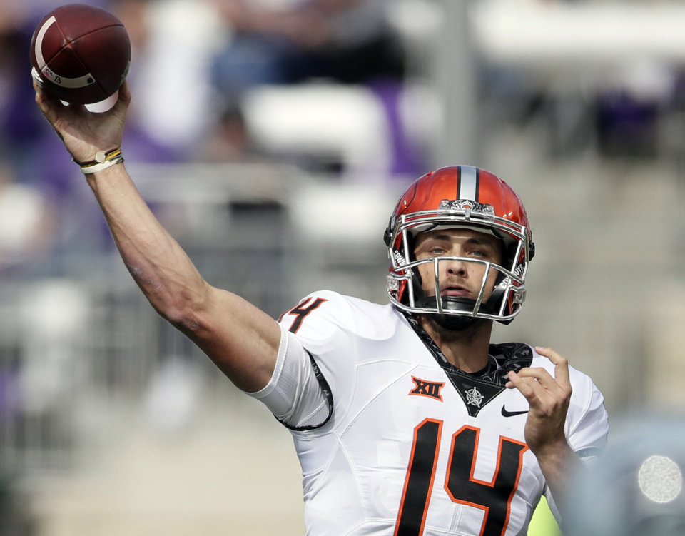 Photo - Oklahoma State quarterback Taylor Cornelius (14) passes to a teammate during the second half of an NCAA college football game against Kansas State in Manhattan, Kan., Saturday, Oct. 13, 2018. (AP Photo/Orlin Wagner)