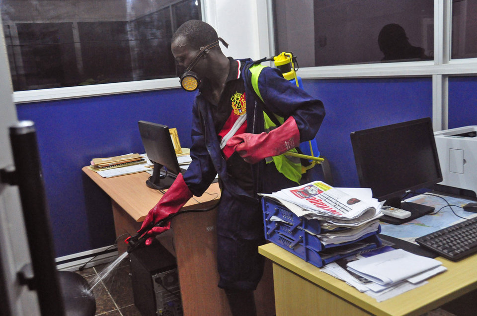 Photo - An employee  of the Monrovia City Corporation sprays disinfectant inside a government building in a bid to prevent the spread of  the deadly Ebola virus, in the city of Monrovia, Liberia, Friday, Aug. 1, 2014. U.S. health officials warned Americans not to travel to the three West African countries hit by the worst recorded Ebola outbreak in history. The travel advisory issued Thursday applies to nonessential travel to Guinea, Liberia and Sierra Leone, where the deadly disease has killed more than 700 people this year. (AP Photo/Abbas Dulleh)