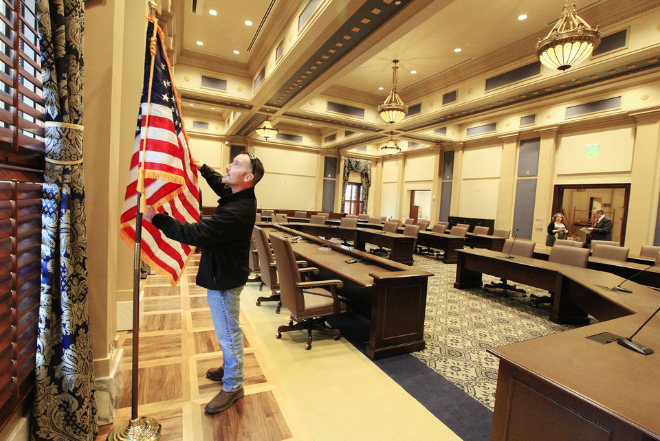 Photo - Adam Cain, state Senate Sergeant at Arms, sets up an American flag in the new Senate Assembly Room on the 5th floor at the state Capitol in Oklahoma City. Final preparations were being made for Monday's arrival of the 2014 Legislature. Photo by Paul B. Southerland, The Oklahoman  PAUL B. SOUTHERLAND - PAUL B. SOUTHERLAND