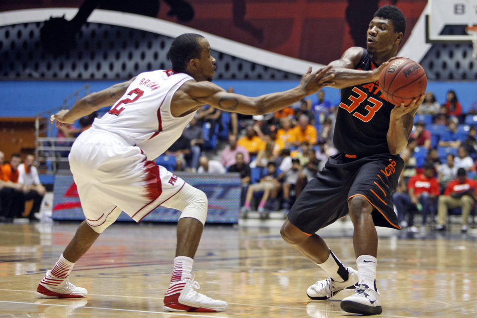 Photo -   NC State's Lorenzo Brown, left, pressures Oklahoma State's Marcus Smart during a NCAA college basketball game in Bayamon, Puerto Rico, Sunday, Nov. 18, 2012. (AP Photo/Ricardo Arduengo)