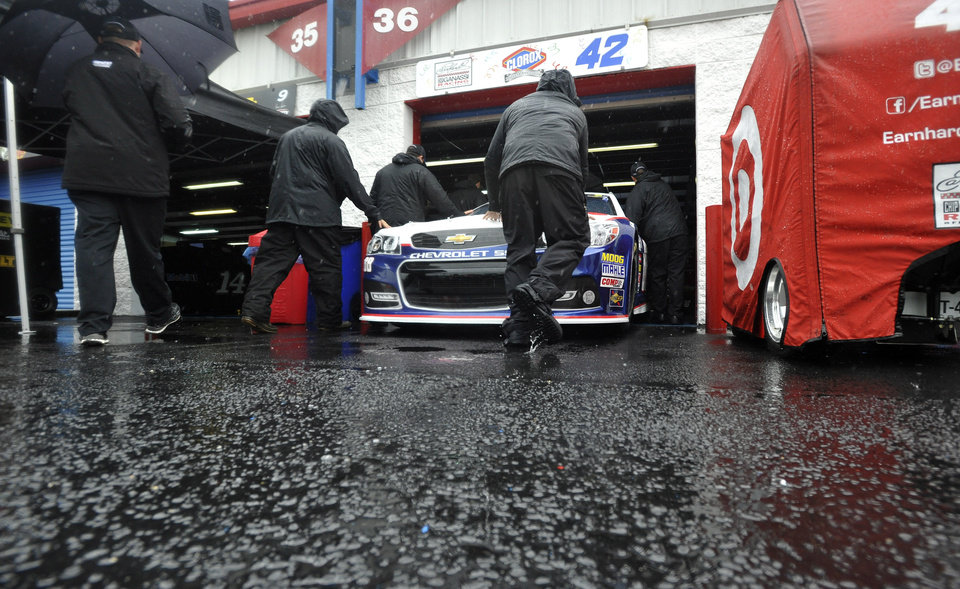 Pit crew members push the car of driver Juan Pablo Montoya into the Grand National Garage at Talladega Superspeedway in Talladega, Ala., Saturday, May 4, 2013. Rain threatens Saturday's qualifying for Sunday's NASCAR Sprint Cup seires Aaron's 499 auto race. (AP Photo/Rainier Ehrhardt)