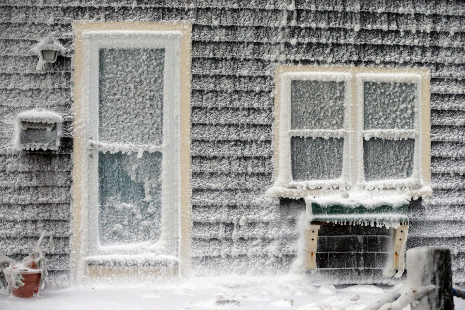 Photo - Ice from breaking waves coats a house along the shore in Scituate, Mass., Friday, Jan. 3, 2014. A winter storm slammed into the U.S. Northeast with howling winds and frigid cold, dumping nearly 2 feet (60 centimeters) of snow in some parts and whipping up blizzard-like conditions Friday. (AP Photo/Michael Dwyer)