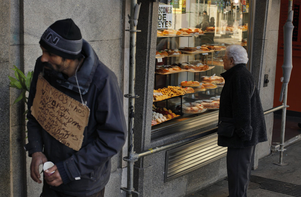 "A man begs money with a banner reading ""I have three kids, help me please, thank you, happy christmas, god bless you"" as a woman looks at  'Three Kings' cakes outside  a bakery shop in Madrid, Sunday, Jan. 6, 2013. (AP Photo/Andres Kudacki)"