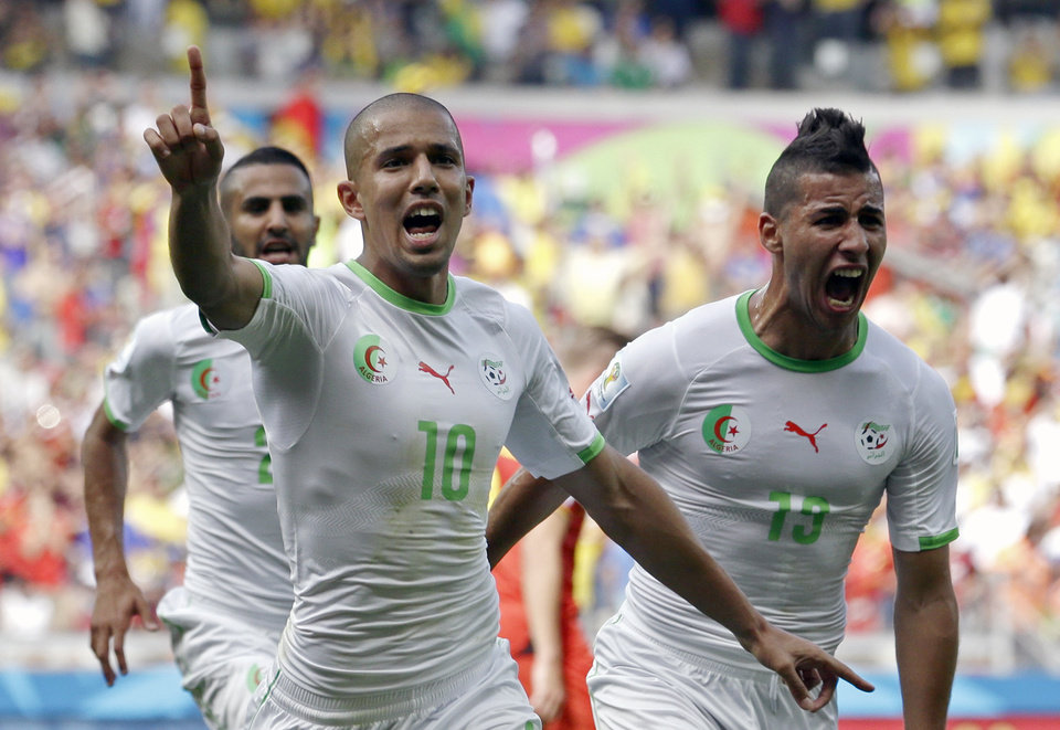 Photo - Algeria's Sofiane Feghouli, left, celebrates after scoring the opening goal during the group H World Cup soccer match between Belgium and Algeria at the Mineirao Stadium in Belo Horizonte, Brazil, Tuesday, June 17, 2014.  (AP Photo/Hassan Ammar)