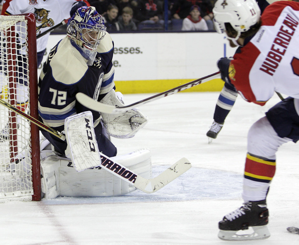 Photo - Columbus Blue Jackets' Sergei Bobrovsky, left, of Russia, makes a save against Florida Panthers' Jonathan Huberdeau during the third period of an NHL hockey game on Saturday, Feb. 1, 2014, in Columbus, Ohio. The Blue Jackets won 4-1. (AP Photo/Jay LaPrete)