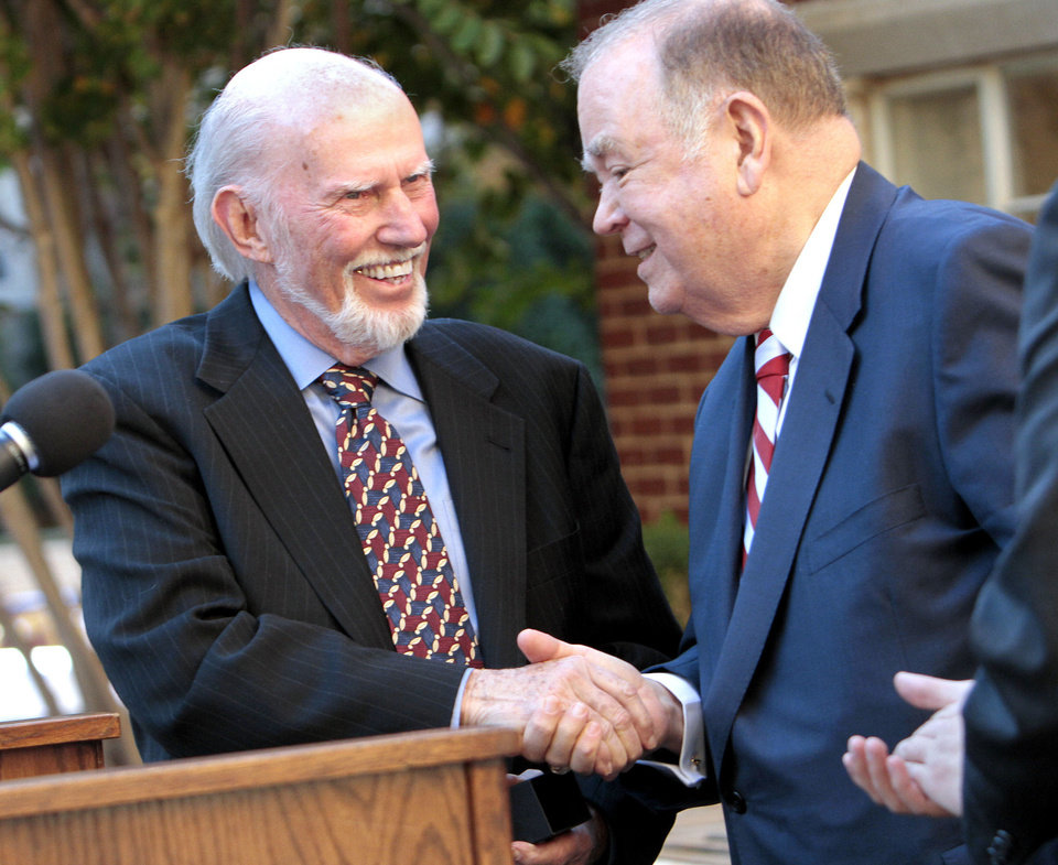 Dr. Tom Boyd, left, a philosophy professor at Oklahoma University, is honored at the annual Ring Ceremony on Friday in Norman. Presenting the ring is OU President David Boren. Photo by Steve Sisney, The Oklahoman