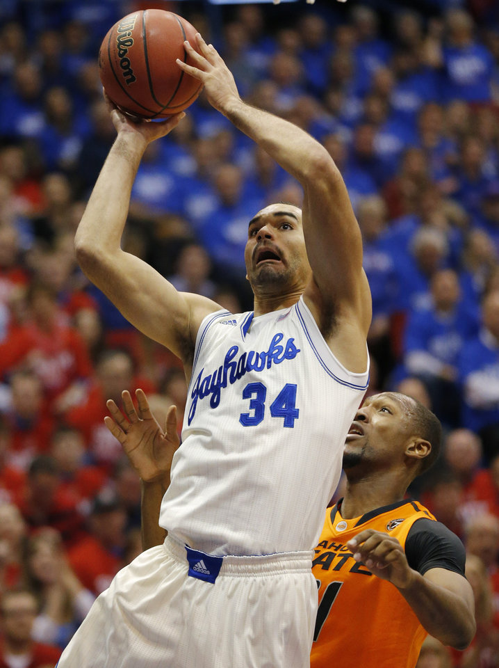 Photo - Kansas forward Perry Ellis (34) shoots while covered by Oklahoma State forward/center Kamari Murphy (21) during the first half of an NCAA college basketball game at Allen Fieldhouse in Lawrence, Kan., Saturday, Jan. 18, 2014. (AP Photo/Orlin Wagner)