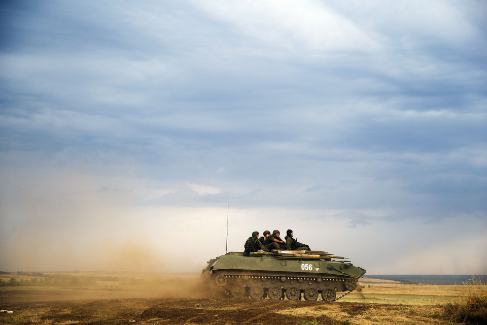 Photo - A Russian APC moves in a field in about 10 kilometers (6.2 miles) from the Russia-Ukrainian border control point at Russian town of Donetsk, Rostov-on-Don region, Monday, Aug. 18, 2014. (AP Photo/Pavel Golovkin)