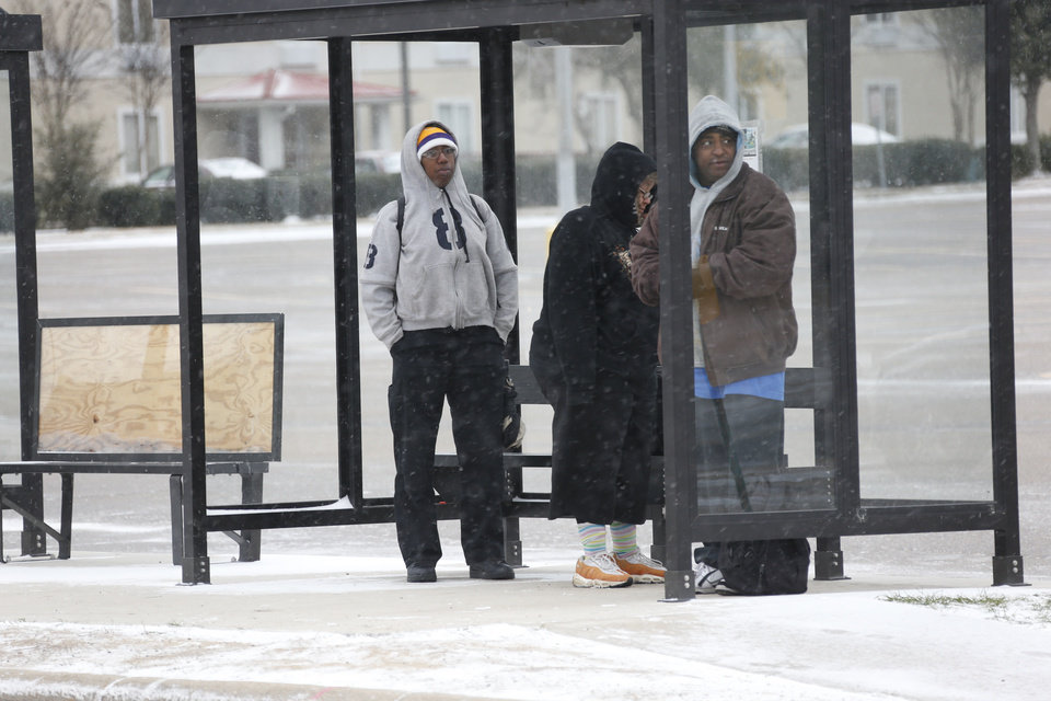 Photo - People wait in a bus shelter in north Jackson, Miss., Tuesday, Jan. 28, 2014 as ice and snow flurries cause difficult driving conditions. A severe winter storm is expected to hit the state bringing ice and snow to the Gulf Coast. (AP Photo/Rogelio V. Solis)