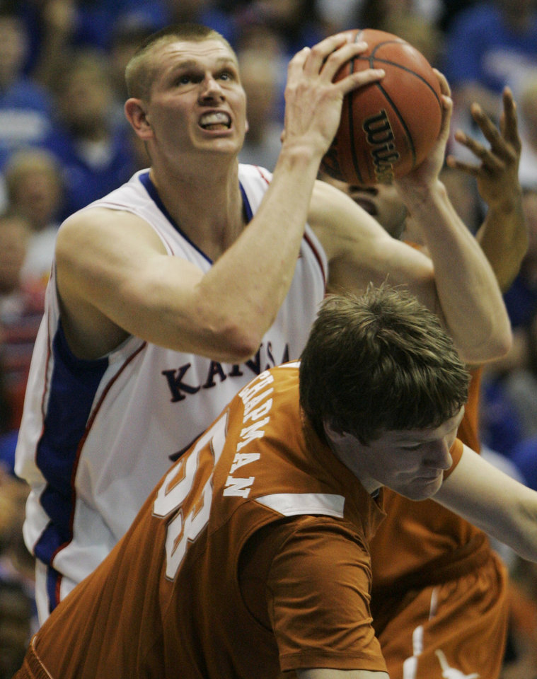 Photo - Kansas center Cole Aldrich (45) is called with charging against Texas forward Clint Chapman (53) during the first half of an NCAA college basketball game in Lawrence, Kan., Saturday, March 7, 2009. (AP Photo/Orlin Wagner) ORG XMIT: KSOW102