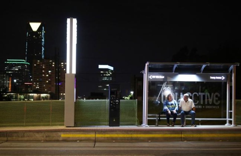Photo -  A couple wait for the OKC Streetcar at the stop on NW 10 Street and Hudson in Midtown. [DOUG HOKE/THE OKLAHOMAN]