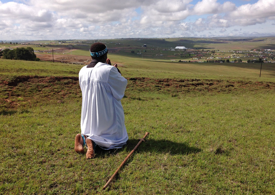 Shembe priest Michael Notychanga prays in the direction of the home of former South African president Nelson Mandela on a hill where in the distance you can see the dome where his funeral service takes place in Qunu, South Africa, Sunday, Dec. 15, 2013. (AP Photo/Akmal Rajput)