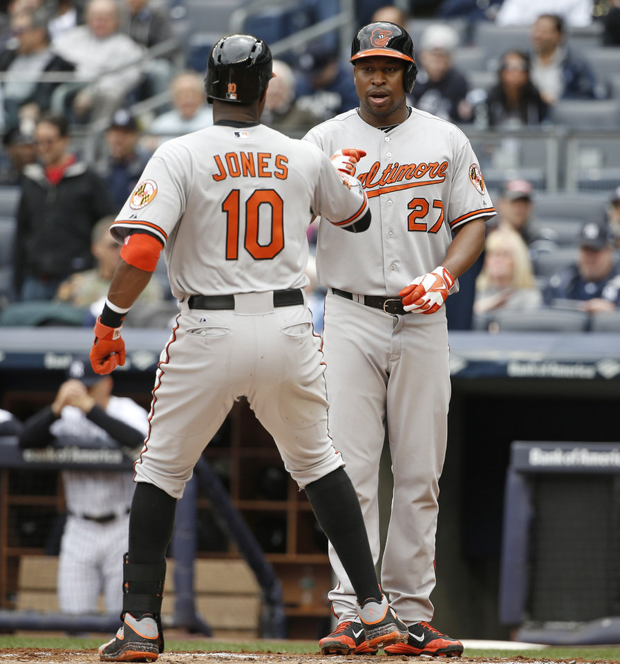 Photo - Baltimore Orioles' Delmon Young greets teammate Adam Jones (10) after scoring on Jones's first-inning, two-run home run off New York Yankees starting pitcher Ivan Nova in a baseball game at Yankee Stadium in New York, Tuesday, April 8, 2014.  (AP Photo/Kathy Willens)