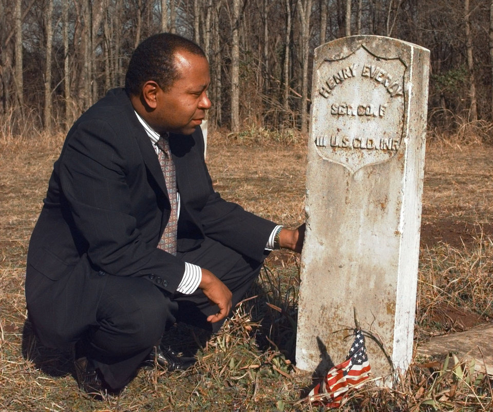 Photo - City of Langston Historian Currie Ballard, at left, kneels beside a tombstone in Langston's Beulahland Cemetery.  Langston takes its name from John Mercer Langston, a 19th-century black abolitionist, lawyer, politician and public speaker.   The town and university have enjoyed disparate fortunes. The university is sparkling clean; it has its own entrance off the highway. The town has not prospered. Abandoned homes and businesses dot the streets.    The town's Beulahland Cemetery holds the graves of former slaves and Civil War soldiers.  Photo by Paul Hellstern,  The Oklahoman Archives