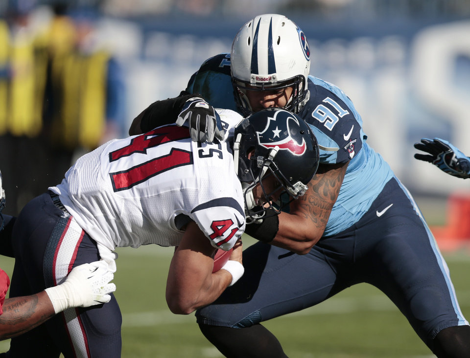 Photo - Houston Texans running back Jonathan Grimes (41) gets past Tennessee Titans defensive end Derrick Morgan (91) as Grimes scores a touchdown on a 3-yard run in the first quarter of an NFL football game Sunday, Dec. 29, 2013, in Nashville, Tenn. (AP Photo/Wade Payne)