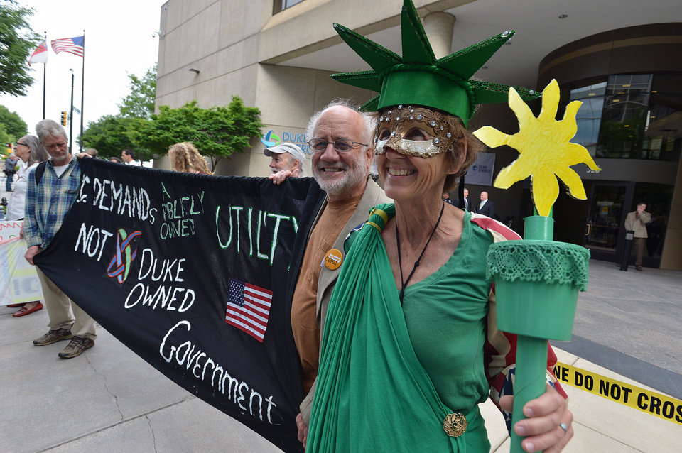 Photo - Concern citizens, Kendell Hale, dressed as Lady Liberty, and her husband Steve Norris from Asheville, N.C. demonstrate with other protesters in front of the Duke Energy office building, Thursday, May 1, 2014, as  shareholders hold their annual meeting in Charlotte, N.C. Some Duke Energy investors plan to push the utility's board of directors to investigate issues surrounding a massive coal ash spill that dumped toxic sludge into a 70-mile stretch of a North Carolina river. (AP Photo/The Charlotte Observer, T. Ortega Gaines) MAGS OUT; TV OUT; NEWSPAPER INTERNET ONLY (REV-SHARE)