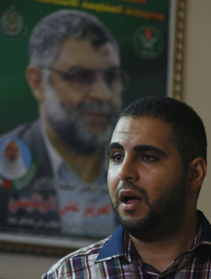Photo - In this Monday, June 24, 2013 photo of Baraa Rantisi, 23, talks at his family house in Gaza City. The picture in the background shows his late uncle of Hamas leader Abdel Azes Rantisi, who was assassinated by Israel in an air strike in 2004. On the day of his induction, Baraa Rantisi was told to wait near a mosque. A white car drove up. Secret passwords were exchanged. And then he was sworn into the Muslim Brotherhood, an exclusive movement that sees itself on a divine mission to establish Islamic rule. AP reporters got rare access to the Rantisi family, the closest thing to a royal clan in the Brotherhood in Gaza, at a time when the movement is under siege throughout the region. (AP Photo/Hatem Moussa)