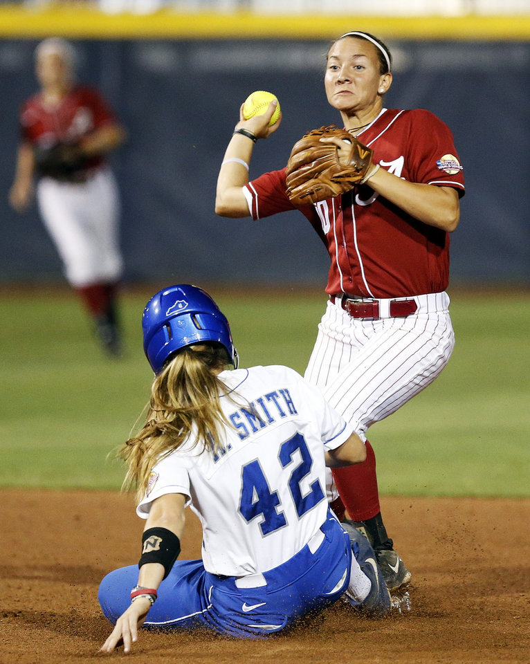 Photo - Alabama's Kaila Hunt (10) throws over Kentucky's Ansley Smith (42) to complete the double play and end the game in the 7th inning during Game 6 of the Women's College World Series softball tournament between Alabama and Kentucky at ASA Hall of Fame Stadium in Oklahoma City, Friday, May 30, 2014. Alabama won, 2-0. Photo by Nate Billings, The Oklahoman