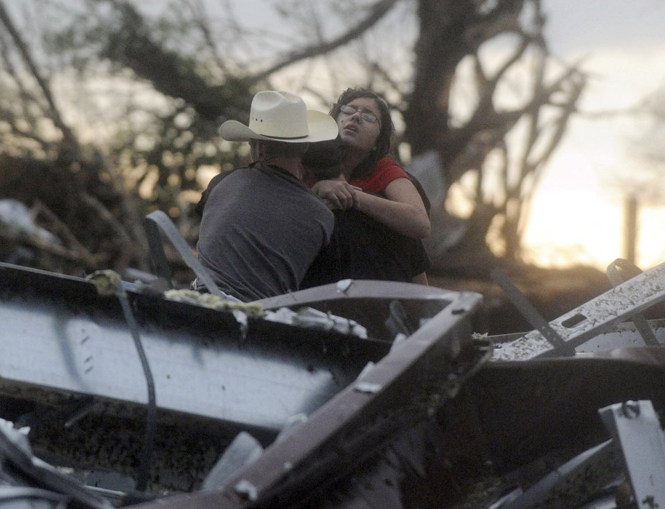 Photo - Two rescuers try to pull free a woman from a destroyed building in Joplin, Mo. after a tornado struck the city on Sunday evening, May 22, 2011. (AP Photo/The Joplin Globe, Roger Nomer) ORG XMIT: MOJOP104