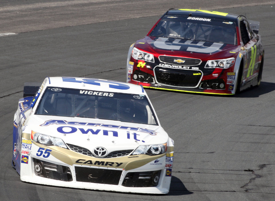Photo - Driver Brian Vickers races ahead of Jeff Gordon during the final practice before Sunday's Sprint Cup Series auto race at New Hampshire Motor Speedway, Saturday, July 12, 2014, in Loudon, NH (AP Photo/Jim Cole)