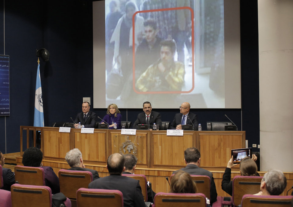 Photo - The image of two Iranian who were traveling with stolen passports on a missing Malaysia Arlines jetliner is displayed on a screen during a presser at the Interpol headquarters in Lyon, central France, Tuesday, March 11, 2014.  (AP Photo/Laurent Cipriani)
