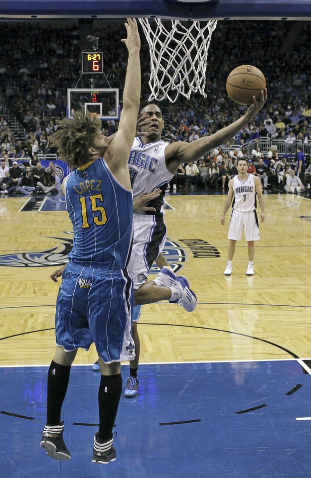 Orlando Magic\'s Arron Afflalo, right, takes a shot as New Orleans Hornets\' Robin Lopez (15) defends during the first half of an NBA basketball game on Wednesday, Dec. 26, 2012, in Orlando, Fla. (AP Photo/John Raoux)