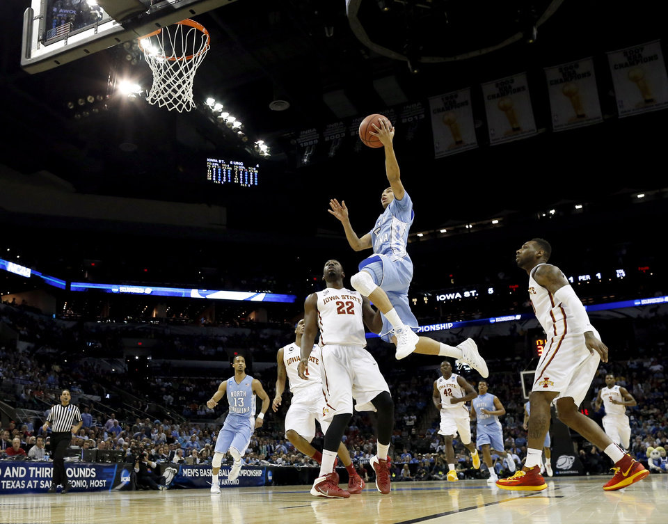 Photo - North Carolina's Marcus Paige (5) goes up for a shot as Iowa State's Dustin Hogue (22) defends during the first half of a third-round game in the NCAA college basketball tournament Sunday, March 23, 2014, in San Antonio. (AP Photo/David J. Phillip)