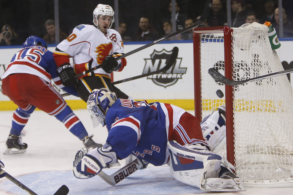 Calgary Flames' Curtis Glencross, second from left, scores a goal against New York Rangers goalie Henrik Lundqvist, of Sweden, during the first period of an NHL hockey game Sunday, Dec. 15, 2013, in New York. (AP Photo/Jason DeCrow)