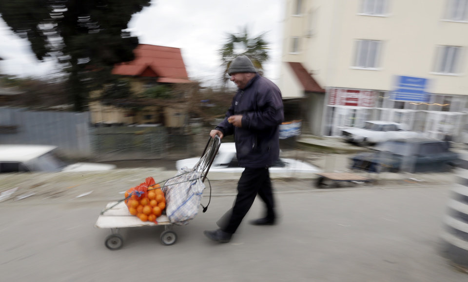 Photo - A man walks with his cart full of tangerines at the Abkhazian border Wednesday, Feb. 5, 2014, near Sochi, Russia. Abkhazia is a festering geopolitical sore, and the economic system still operating in these and many other parts of Russia is decidedly 19th century. As Russia opens its doors to a curious world with the Sochi Games, places like this border expose the vast contradictions still gripping the one-time superpower 21 years after the Soviet Union collapsed. (AP Photo/Morry Gash)