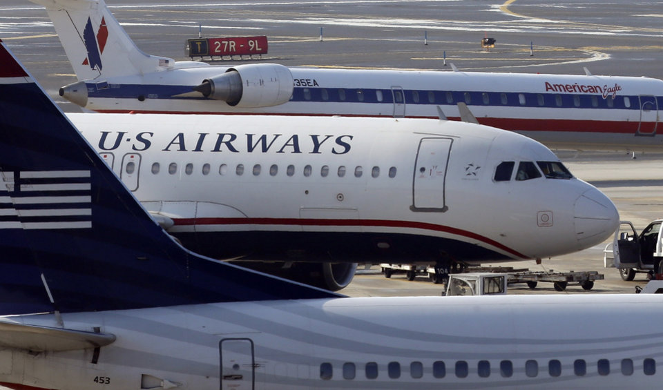 Photo - American Airlines and US Airways jets park at gate at the Philadelphia International Airport, Thursday, Feb. 14, 2013, in Philadelphia. The merger of US Airways and American Airlines has given birth to a mega airline with more passengers than any other in the world. (AP Photo/Matt Rourke)