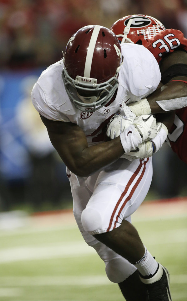 Photo - Alabama running back T.J. Yeldon (4) scores a touchdown against Georgia safety Shawn Williams (36) during the second half of the Southeastern Conference championship NCAA college footballgame, Saturday, Dec. 1, 2012, in Atlanta. (AP Photo/Dave Martin)