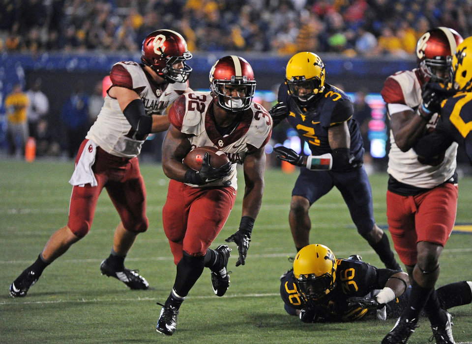 Photo - Oklahoma's Samaje Perine (32) runs for a first down during the fourth quarter of an NCAA college football game against West Virginia in Morgantown, W.Va., on Saturday, Sept. 20, 2014. (AP Photo/Tyler Evert)