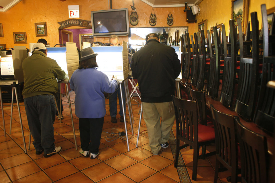 Voters cast their ballots in a Mexican restaurant turned polling place, on election day on the South Side of Chicago Tuesday Nov. 6, 2012. (AP Photo/Jerome Delay)